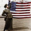 Young woman in military uniform holding up an American flag — Stock Photo