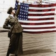 Young woman in military uniform holding up an American flag — Stock Photo #12302868
