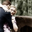 Young woman embracing a man and pointing towards an information board — Stock Photo #12302880