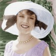 Woman in a wide brimmed hat smiling — Stock Photo