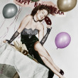 Young woman sitting on a table with balloons and sign — Stock Photo