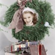 Stock Photo: Young womlooking through wreath with presents in front of her