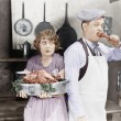 Couple standing together in kitchen with cooked turkey — Foto de stock #12302924