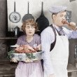 Foto Stock: Couple standing together in kitchen with cooked turkey