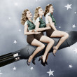 Foto Stock: Three women sitting on rocket