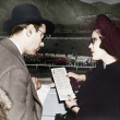 Elegant couple at a horse race looking at a program - Stock Photo