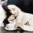 Nun sipping tea out of a teacup with a straw  — Stock Photo