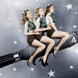 Three women sitting on a rocket - Stock Photo