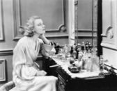 Kobieta siedzi na jej próżność, patrząc w lustro — Zdjęcie stockowe
