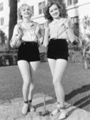 Two young women standing together playing horse shoes — Stock Photo