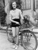 Woman next to her bicycle with her dog in the basket — Stock Photo