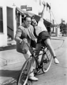 Man trying to balance an exuberant woman on a bicycle — Stock Photo