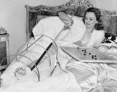 Woman in bed trying to scratch her broken foot with a pole — Stock Photo