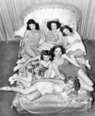 Six smiling young women lying on a bed — Stock Photo