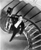 Elegant man looking up from the bottom of a staircase — Stock Photo