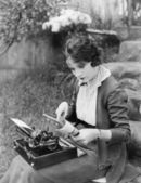 Woman sitting in the yard with a typewriter on her lap — Stock Photo