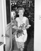 Woman walking through a doorway with flowers in her hands — Stock Photo