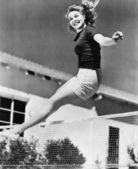 Woman leaping over a tennis net — Stock Photo