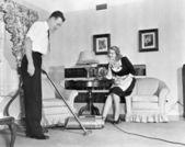 πωλητής καταδεικνύει μια ηλεκτρική σκούπα για μια νοικοκυρά στο σπίτι της — Φωτογραφία Αρχείου