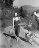 Woman walking her Collie on a country road — Stok fotoğraf