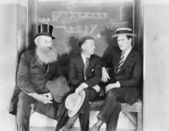 Three men sitting on a bench — Stock Photo
