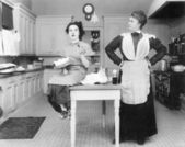 Gospodyni w kuchni, wpatrując się w młodą kobietę, jeść tort — Zdjęcie stockowe