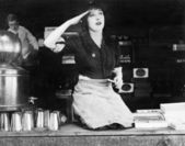 Woman kneeling on the counter of a bar and saluting — Stock Photo