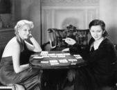 Two women sitting together playing cards — Stock Photo