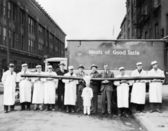 Butchers showing off a long sausage in front of a truck — Stock Photo