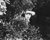Woman peeking through bushes — Stockfoto
