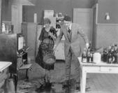 Mannen och kvinnan tittar på spilld vätska på köksgolvet — Stockfoto