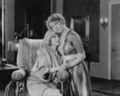 Young woman consoling her friend in wheelchair — Stock Photo