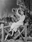 Ahşap korkuluk üzerine oturan kadın — Stok fotoğraf