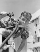 Young man drinking water from hose — Stock Photo