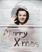 Woman waving at window with Christmas greeting — Stockfoto