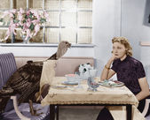 Woman eating meal at table with live turkey — Stockfoto