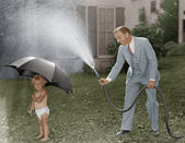 Toddler and dad playing with hose in yard — Stock Photo