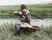 Female hunter with gun near river — Stock Photo