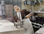 Man with tie stuck in meat grinder — Stockfoto