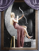 Woman sitting on crescent moon with bow and arrow — Stock Photo