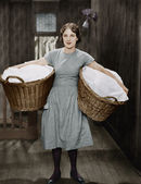 Woman carrying laundry baskets — Stock Photo