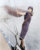 Woman leaning off boat into the wind — Stock Photo