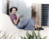 Ung kvinna sitter på en terrass leende och äta vindruvor — Stockfoto