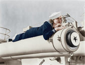 Woman in a sailors uniform lying on a cannon — Stock Photo