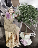 Woman sitting on a crate of oranges next to a plane and citrus tree — Stock Photo