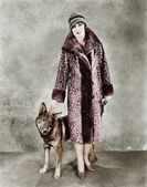 Woman in her Giraffe patterned fur coat and her dog — Stock Photo