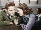 ζευγάρι σε ένα εστιατόριο κοιτάζοντας ο ένας τον άλλον και μοιράζονται ένα κούνημα γάλακτος με δύο καλαμάκια — Φωτογραφία Αρχείου