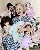 Retrato de una mujer rodeada de muñecas y sonriendo — Foto de Stock