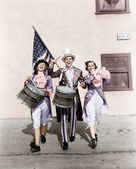 Marching band performing in a parade with an American flag — ストック写真