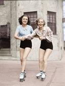Portret van twee jonge vrouwen met roller blades schaatsen op de weg en glimlachen — Stockfoto